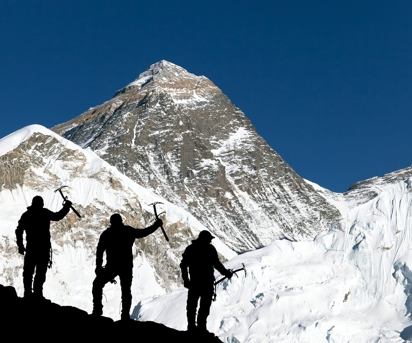 Mount Everest from Kala Patthar from Kala Patthar and silhouette of climbing men with ice axe in hand - trek to everest base camp - Nepal