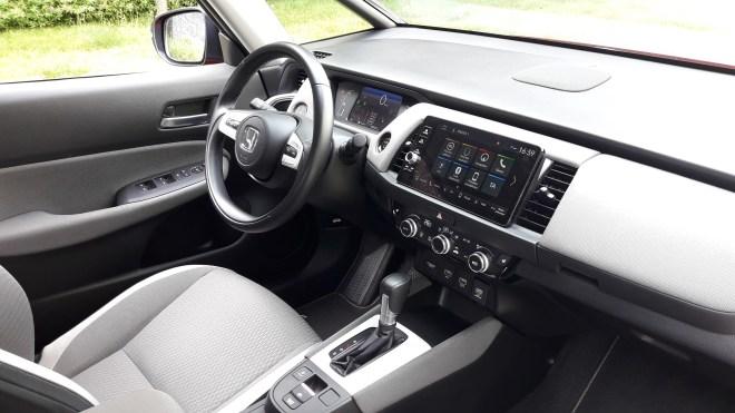 Volič jízdních režimů oproti většímu modelu CR-V Hybrid nesuplují tlačítka, ale je jím hezky do ruky padnoucí klasická páka. (foto Vladimír Löbl)