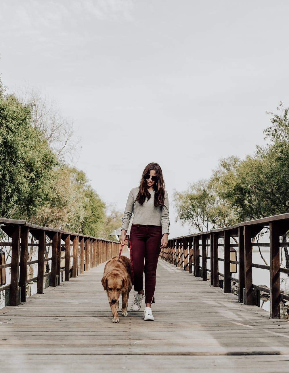 photo of woman walking on dock with her dog