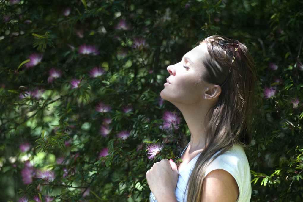 woman closing her eyes against sun light standing near purple petaled flower plant