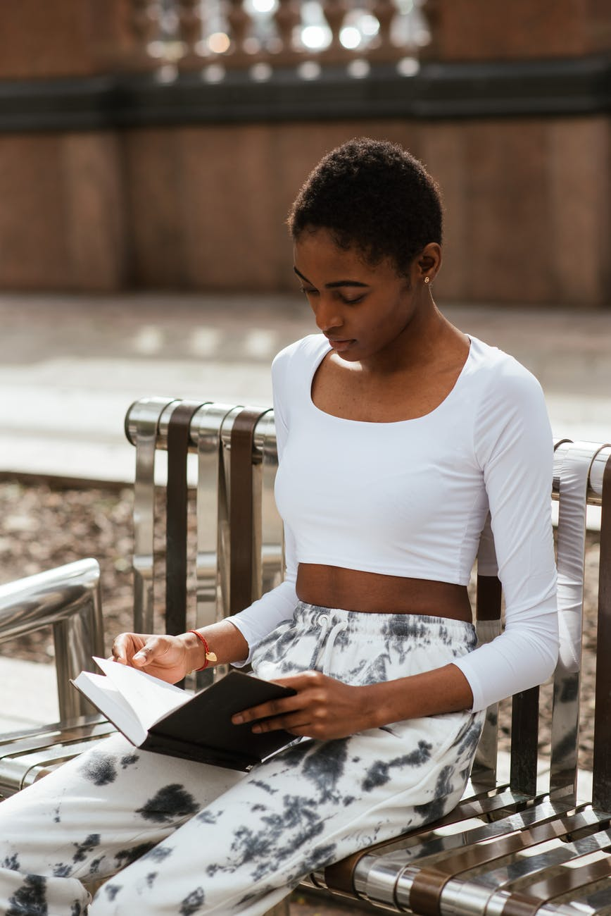 pensive black woman reading book on bench