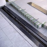 Expansion Joint Coverplates replaced SJS SYSTEM supplied with integral hanger bars is laid out next to joint opening. Blockouts left by previous failed system have been filled with EMSEAL elastomeric, sound-absorbing nosing material.