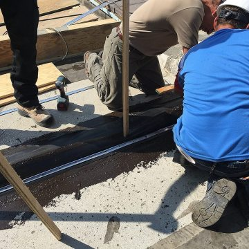 RoofJoint lower flange secured to deck with termination bar and concrete anchors.