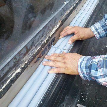 La espuma precomprimida de la junta DSM-FP se instala entre un pared y las patas de soporte