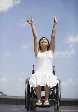 Photo of female in a manual wheelchair raising her arms in the air