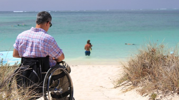 Photo of man in manual wheelchair on the beach