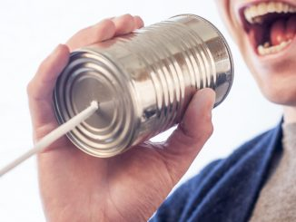 Photo of a man speaking through a tin can with a string