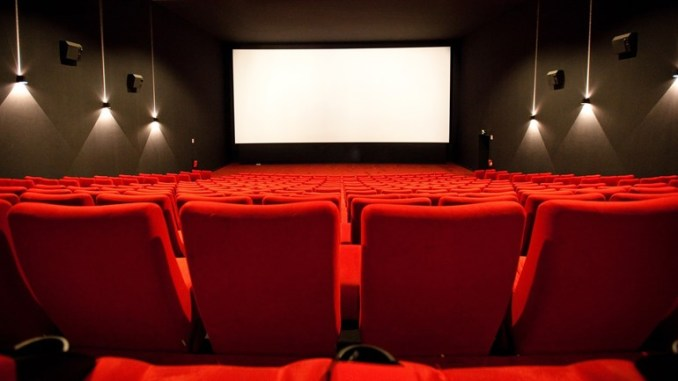 Inside a movie theatre with rows of red seats, hanging lights on the parallel walls to the front of the theatre where a large rectangular white screen