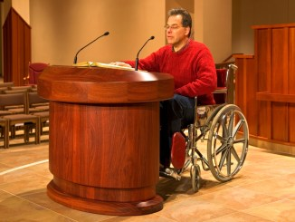 Photo of a man in a manual wheelchair giving a talk at the podium at a place of worship