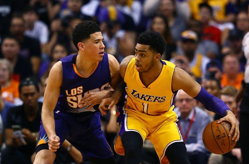 Mar 23, 2016; Phoenix, AZ, USA; Los Angeles Lakers guard D'Angelo Russell (right) controls the ball against Phoenix Suns guard Devin Booker at Talking Stick Resort Arena. The Suns defeated the Lakers 119-107. Mandatory Credit: Mark J. Rebilas-USA TODAY Sports
