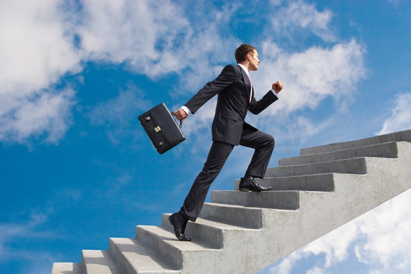 a picture of a man in a suit climbing a staircase into the sky. industry 4.0 will play a large part in how factory workers become more specialized and advance their careers.