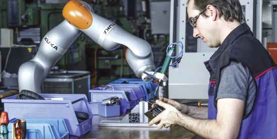 a picture of a single arm KUKA-made robot and manufacturing employee working simultaneously as an assembly station.