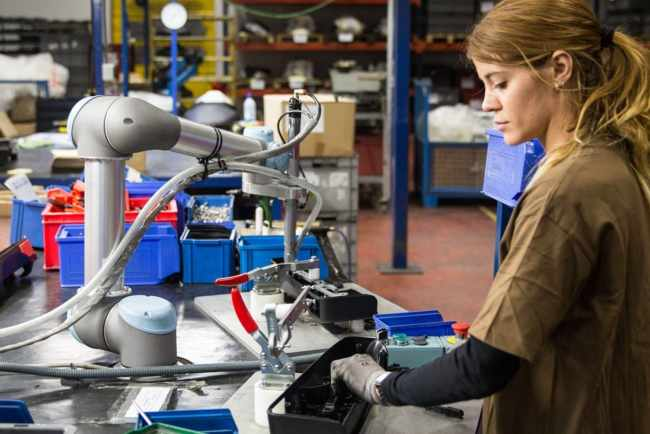 A picture of a worker and cobot working in manufacturing facility where collaborative robotics are in use