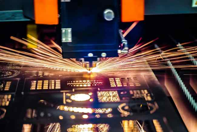 A photo of a CNC machine cutting metal shapes and forms where data is fed from ERP systems.