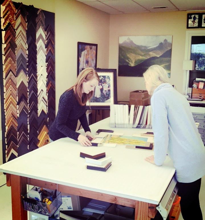 Sara choosing matting and framing for a customer