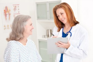 Physician taking notes while talking to a patient