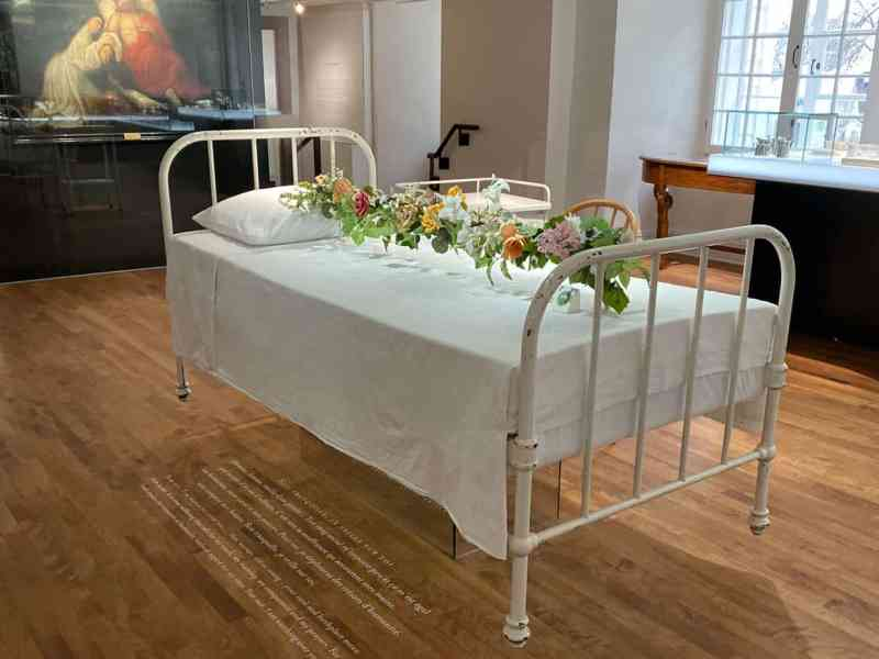 Hospital bed with flowers above - museum exhibit at Le Monastere des Augustines