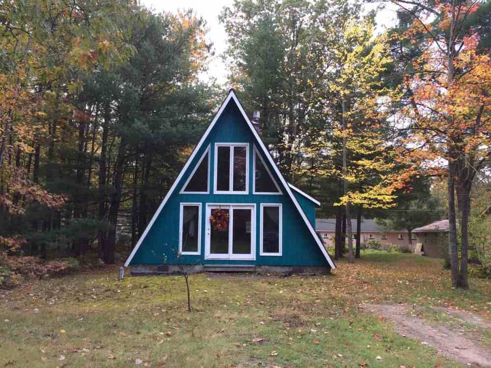 A blue teal A-frame cabin in autumn