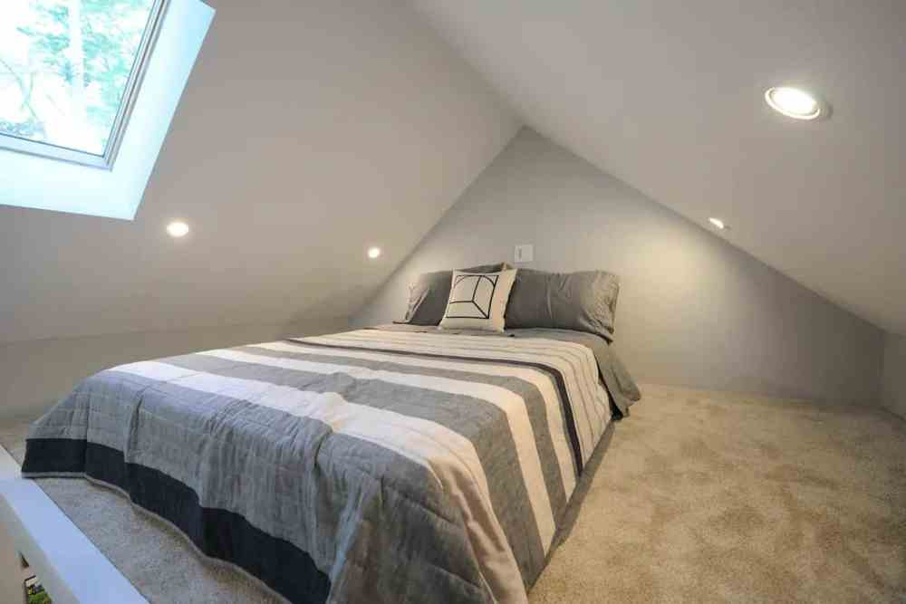 Sleeping loft with grey striped mattress in a Michigan tiny house.