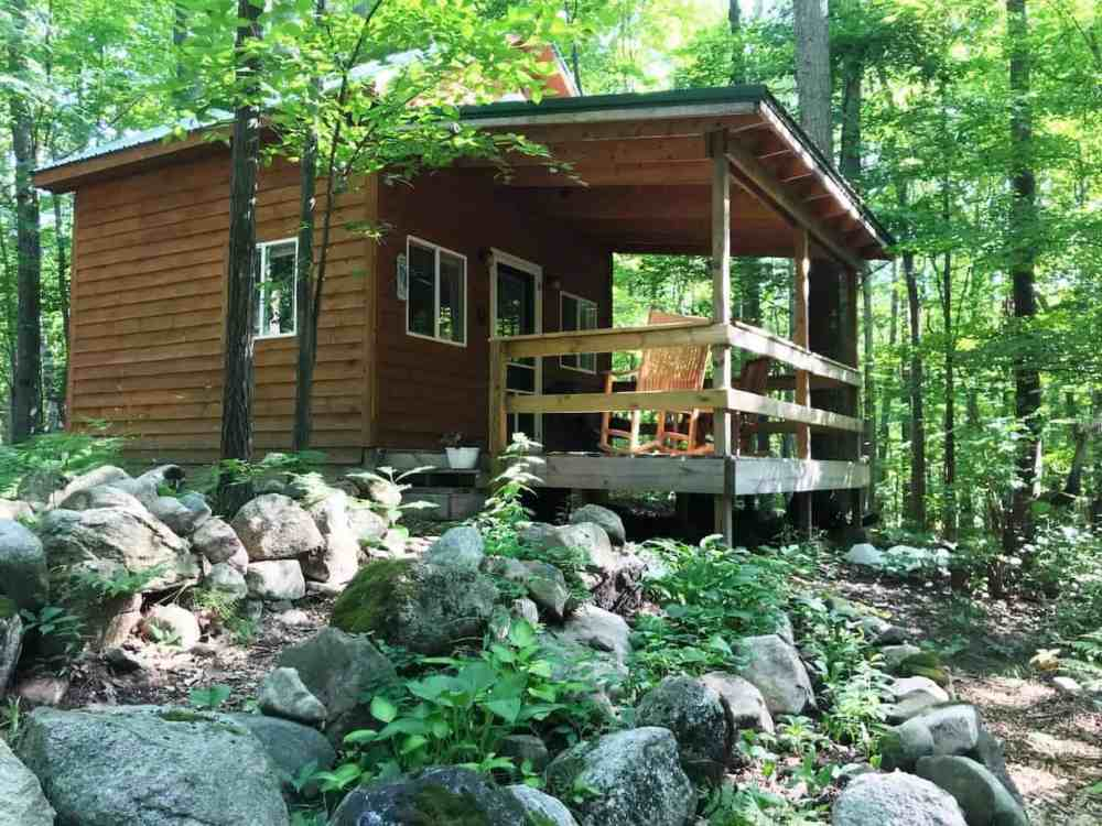 A tiny house with a roofed porch in the woods.
