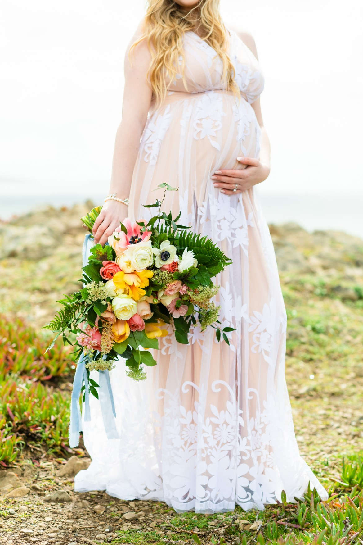 Shannon wears an off white dress to show off her pregnancy. The photo is cropped at the top of her pregnant belly. She holds a bouquet of colorful and bright flowers.