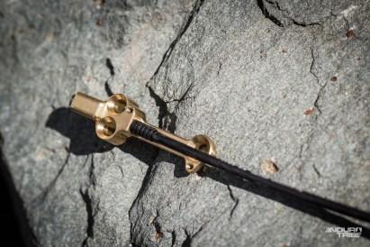À son extrémité, dans le tube supérieur et plus précisément au niveau de la jonction avec le tube de selle, le câble vient se loger dans cette pièce dorée, vissée et donc solidaire du châssis.