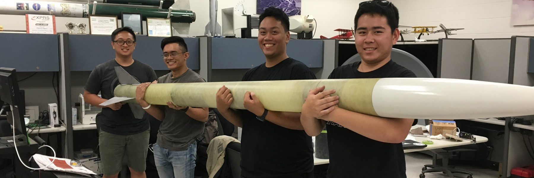 Four men holding an 11' rocket.