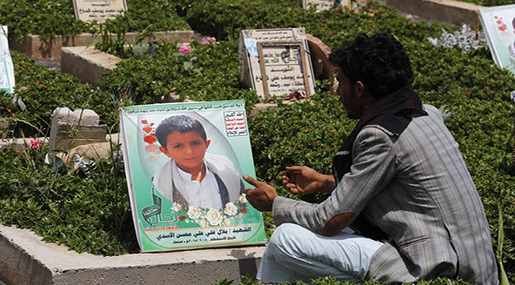 A Yemeni father sitting next to his son's grave