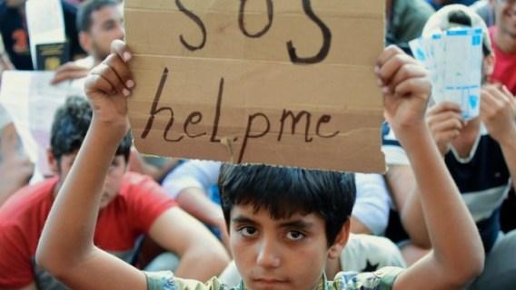 """Niño migrante sostiene un cartel que dice """"SOS ayúdame"""", delante de la estación de trenes Keleti (este) en Budapest el 2 de septiembre de 2015. (AFP PHOTO / ATTILA KISBENEDEK)"""