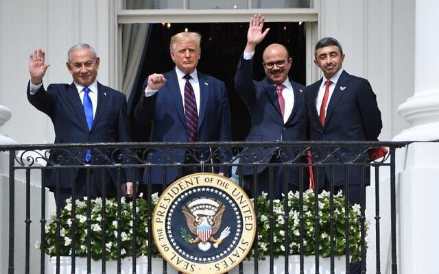 De iquierda a derecha saludando desde el balcón de la Casa Blanca están Netanyahu, con la mano derecha levantada, Trump con el puño cerrado en alto, el minstro de Barein con la mano derecha levantada y el ministro de EAU con las manos hacia atrás