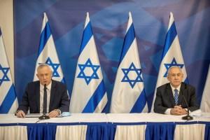 Gantz y Netanyahu sentados delante de banderas de Israel