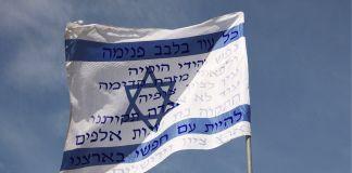 Una bandera de Israel con la letra del Hatikva en hebreo