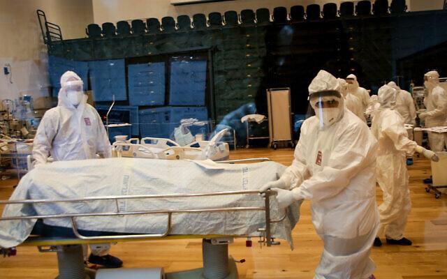 Personal sanitario con equipos blancos de protección contra el virus en una sala, dos de ellos arrastran una camilla con una persona fallecida cubierta por uan sábana blanca.