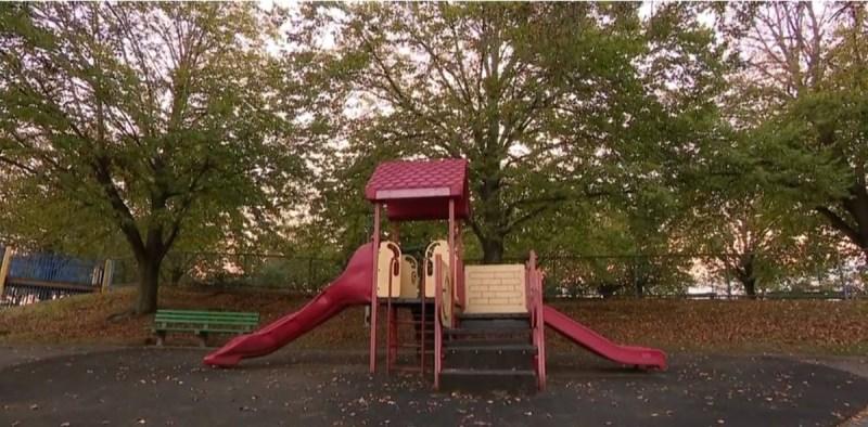 un parque de recreo con juegos infantiles metálicos sobre césped y rodeado de árboles