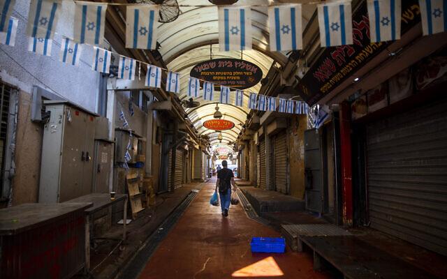 Una calle larga del mercado con todos los negocios cerrados por la que camina un hombre cargando unas bolsas, banderas israelíes cuelgan de lado a lado de la calle