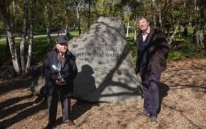 a la izquierda un hombre bajo, a la derecha uno alto vestidos con ropa de abrigo a los lados de una roca conmemorativa del Holocausto en medio de un bosque