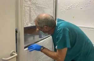 empleado sanitario con ropa verde de hospital, de espalda y agachado guarda vacuna en congelador