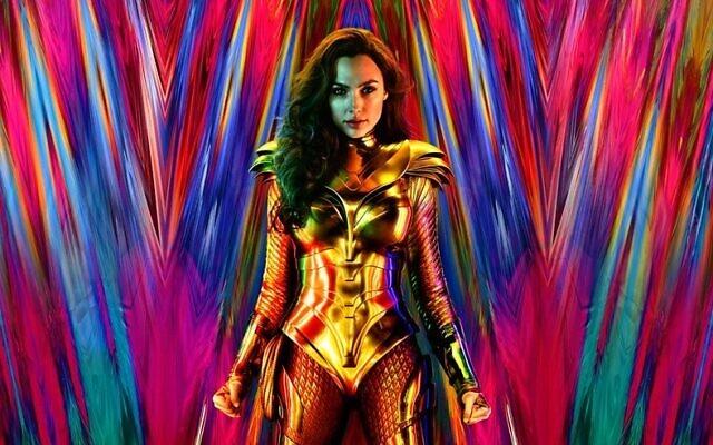 Con telón de fondo estelar de varios colores, la actriz posa vestida con su atuendo de Wonder Woman metálico dorado, su cabellera suelta hacia delante del lado izquierdo y echado atrás del lado derecho. Los brazos firmes a ambos lados del cuerpo con los puños cerrados y un ancho brazalete de metal dorado en cada brazo.