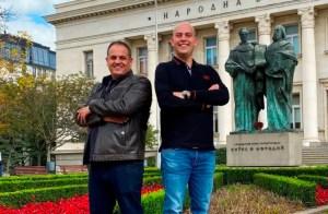dos hombres de diferente estatura y con los brazos cruzados están de pie delante de un edificio estatal en una zona ajardinada y una estatua verde a sus espaldas