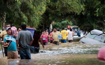 Gente de Honduras transitando una vía inundada en 2020