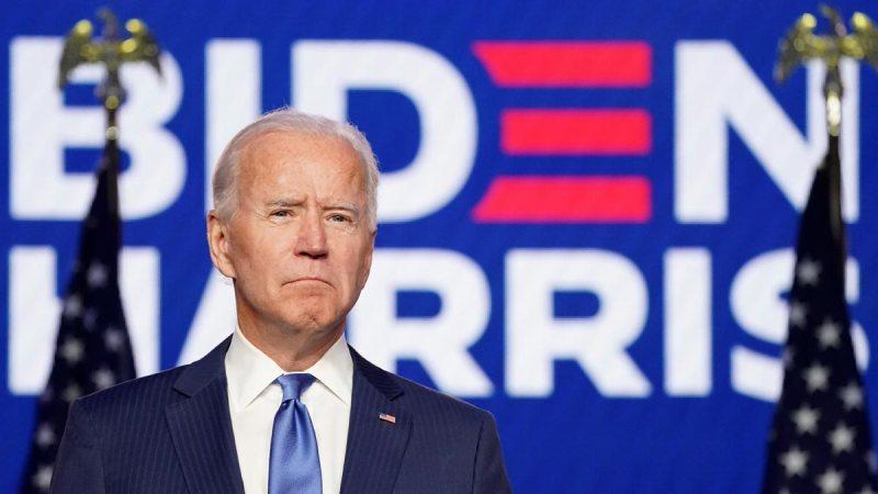 Joe Biden frente a una manta de apoyo a su campaña