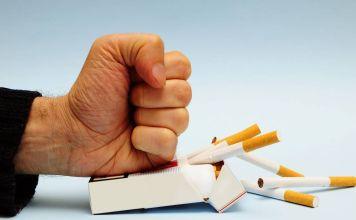 Una mano aplastando una cajetilla de cigarros para dejar de fumar