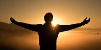 Un hombre frente al atardecer extendiendo los brazos en simbolismo de esperanza o expectativa
