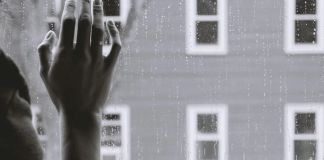 Mano de una mujer recargada en un vidrio de una ventalla en una tarde lluviosa