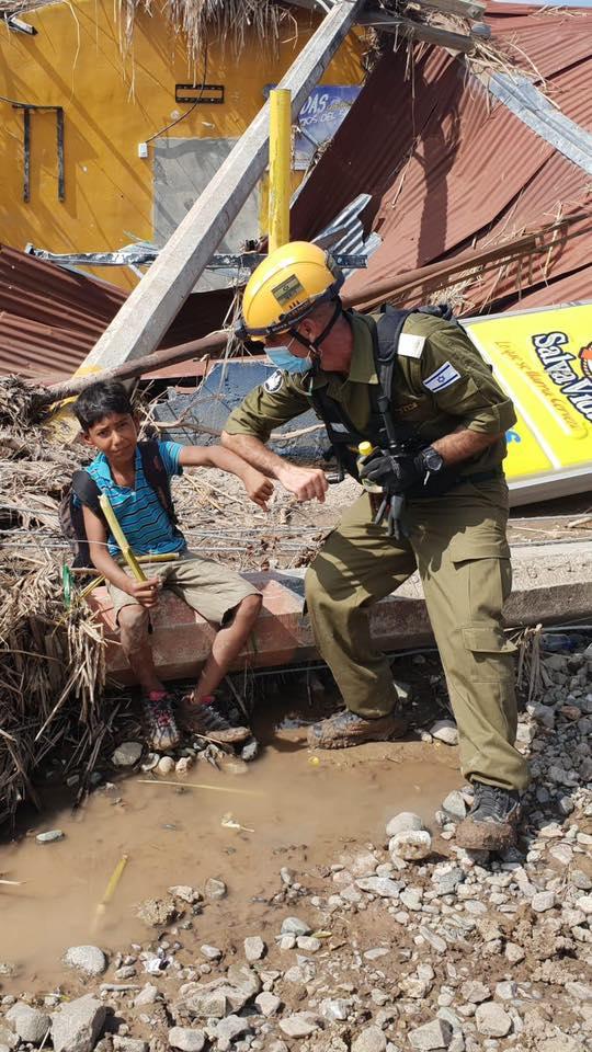 Elemento de la delegación de ayuda israelí conviviendo con un niño lugareño.