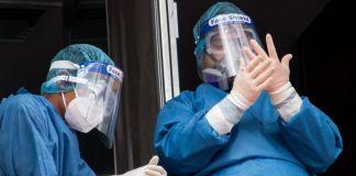 Dos miembros de personal médico con trajes con equipo de protección personal para COVID-19