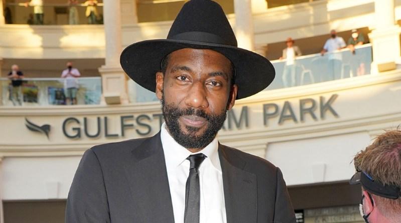 un hombre de color con traje y sombrero negros, y barba oscura