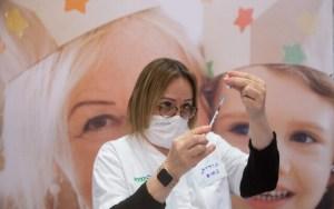 enfermera cargando jeringa con fondo mural de gente sonriente