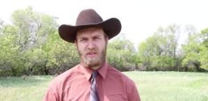 Hombre joven rubio con barba y bigote, camisa rosa, corbata y sombrero