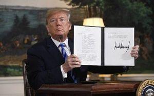 Trump enseña una carpeta abierta con un documento que lleva su firma